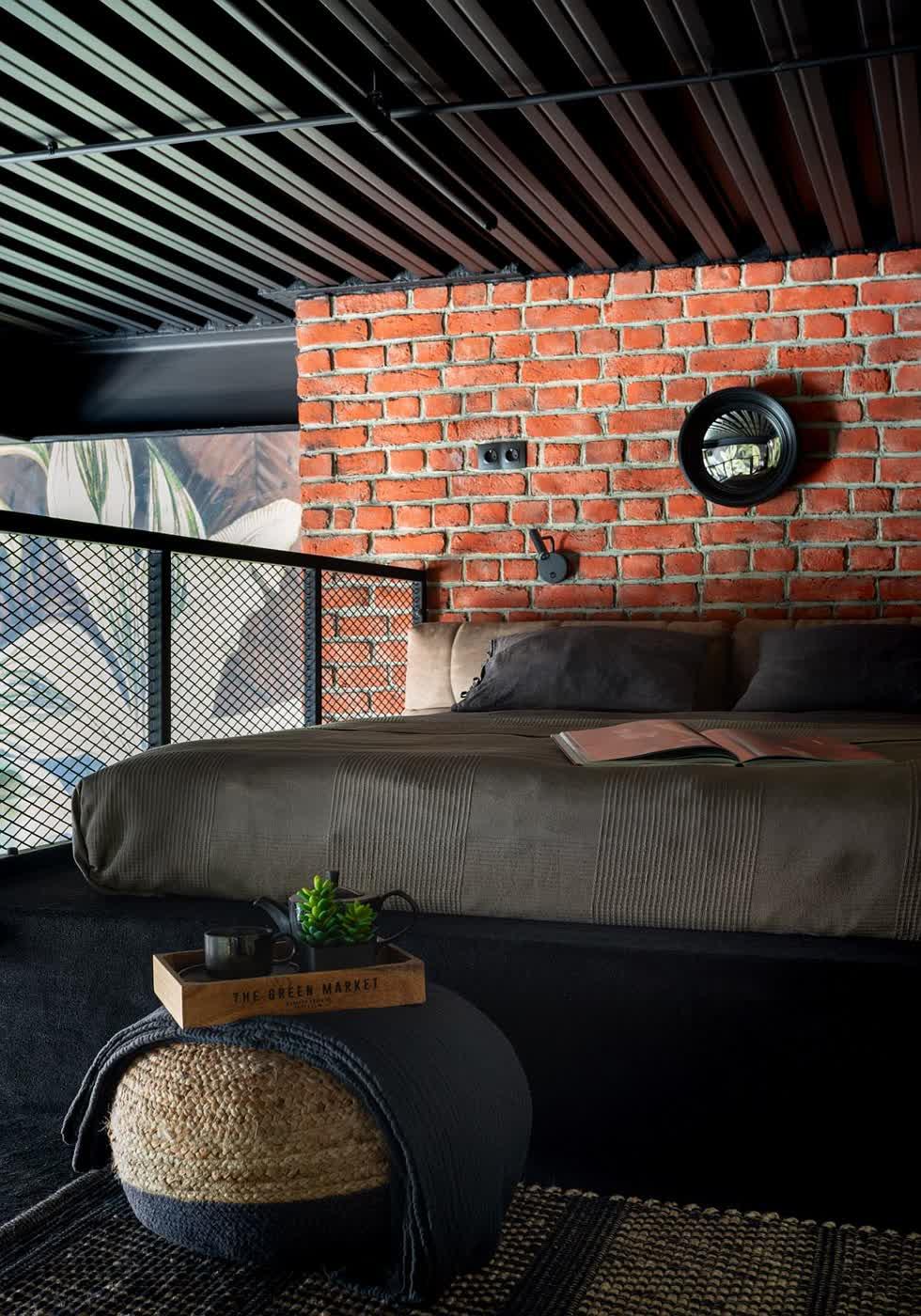 Tường gạch và lưới kim loại thông minh cung cấp sự tương phản kết cấu rộng rãi cho phòng ngủ công nghiệp nhỏ này.