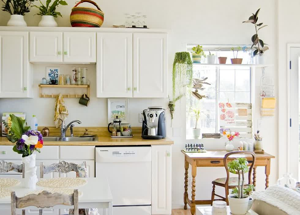 Trồng cây trong nhà mang lại màu xanh cho nhà bếp hiện đại này với màu trắng với phong cách thư thái.