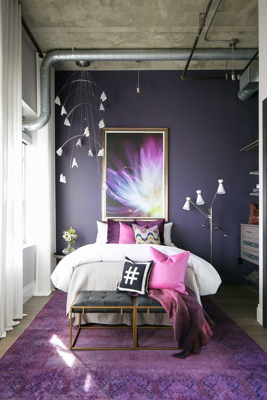 Trần bê tông và ống dẫn tiếp xúc mang lại vẻ đẹp công nghiệp cho phòng ngủ đầy màu sắc này trong căn phòng màu tím này.