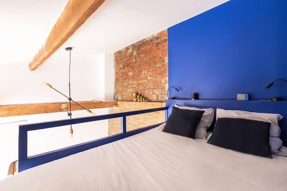 Phòng ngủ công nghiệp nhỏ với bức tường tạo điểm nhấn màu xanh và thiết kế siêu phong cách.