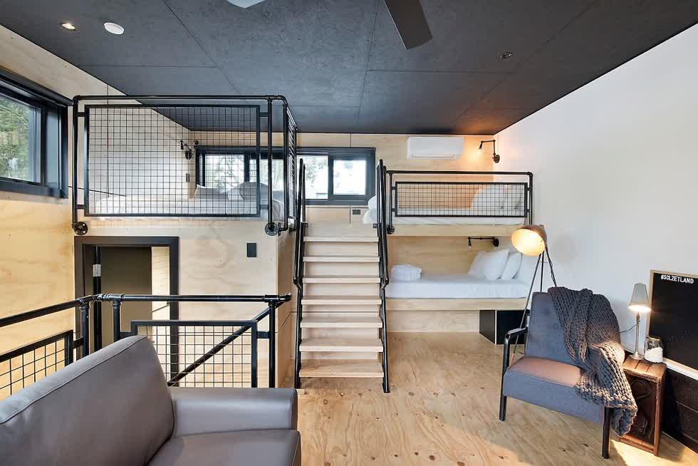 Phòng ngủ công nghiệp hiện đại ở tầng áp mái bằng gỗ được sơn đen với lối trang trí thông minh.