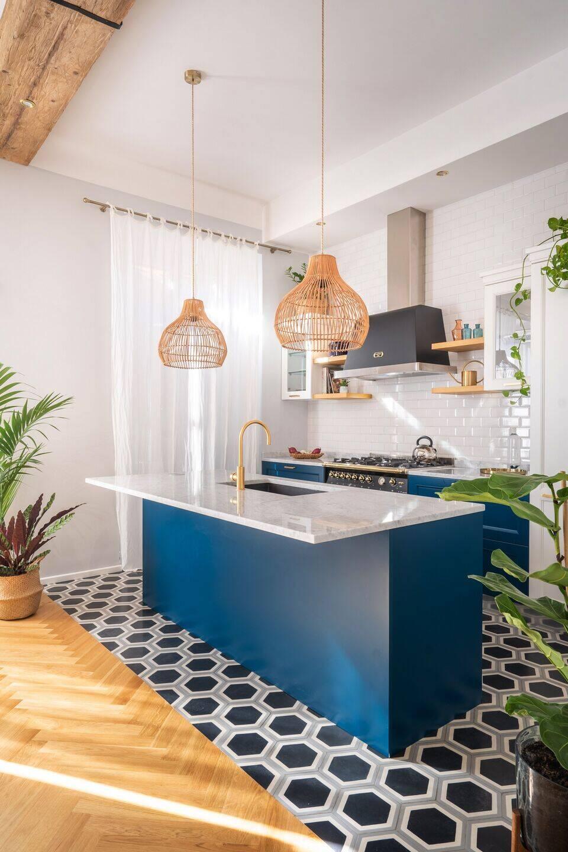 Khu vực bếp nổi bật với hệ tủ bếp màu xanh dương, phối cùng mặt bàn bếp làm từ đá marble trắng. KTS còn bố trí một đảo bếp cùng bộ với tủ bếp nhằm tăng diện tích nấu nướng cũng như tích hợp làm bàn ăn cho gia chủ.