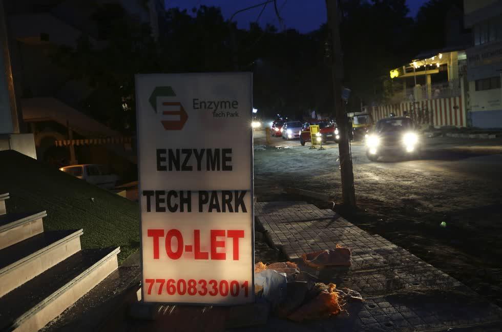 Ô tô chạy ngang qua một tấm biển quảng cáo cho thuê không gian văn phòng ở Bengaluru, Ấn Độ hôm 13/10. Ảnh: AP