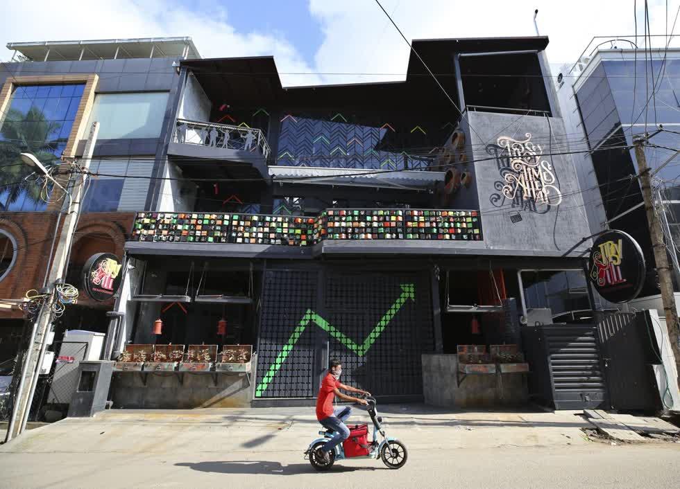 Một người lái xe đi ngang qua một quán bar và nhà hàng nổi tiếng đã đóng cửa do đại dịch COVID-19 ở Bengaluru, Ấn Độ. Ảnh: AP