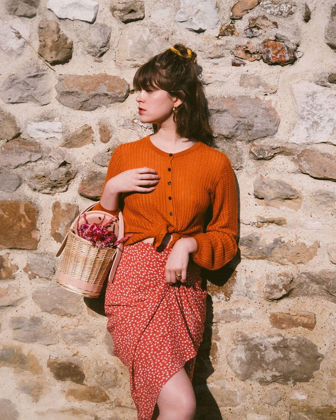 Chân váy hoa nhí màu đỏ và áo cardigan lửng màu cam đất.Ảnh: @apollinethibault