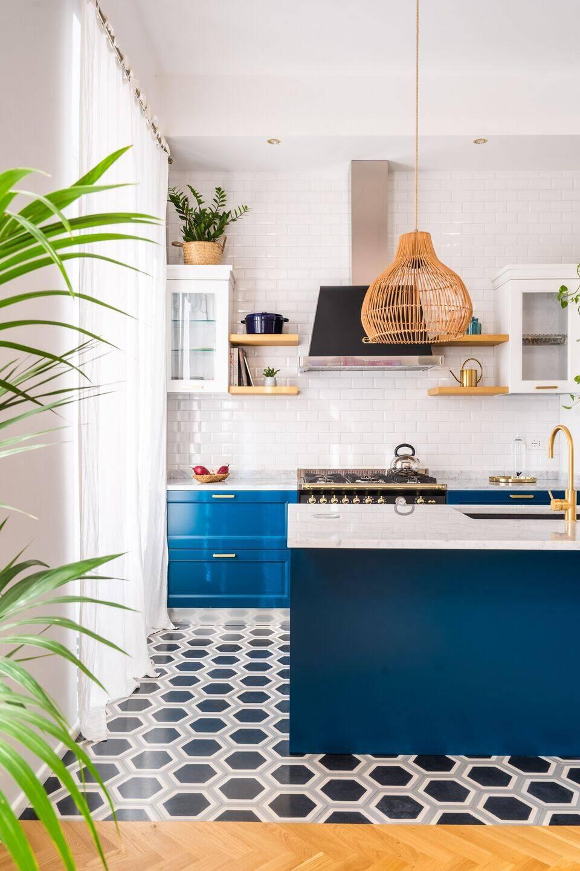 Hệ tủ bếp nổi bật trên nền tường gạch cỡ nhỏ đi ron trắng. Để tối ưu diện tích, các kệ để đồ được đóng cao ở trên tường.