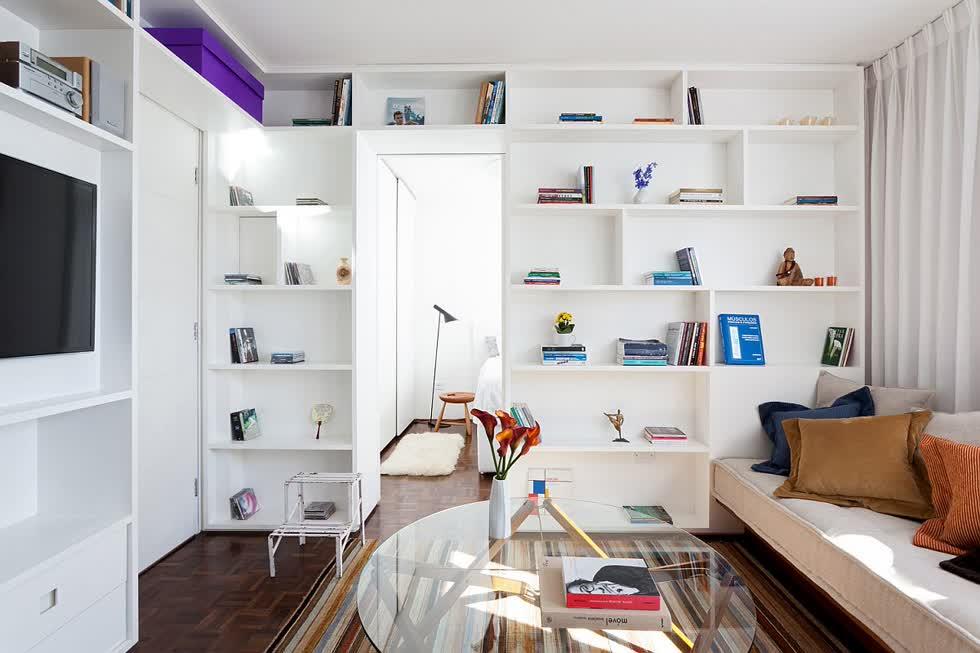 Kệ mở màu trắng vừa cung cấp không gian lưu trữ gọn đẹp, vừa đóng vai trò vách ngăn phòng khách với phòng ngủ trong căn hộ 30m2.