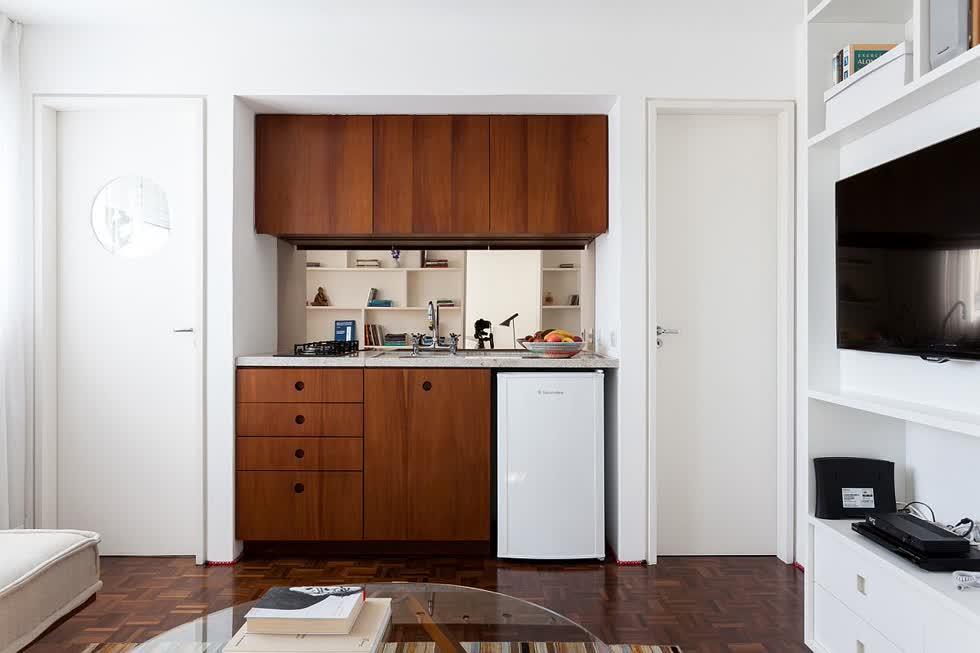 Góc bếp nhỏ được gói gọn trong hốc tường, nổi bật với hệ tủ gỗ màu cánh gián.