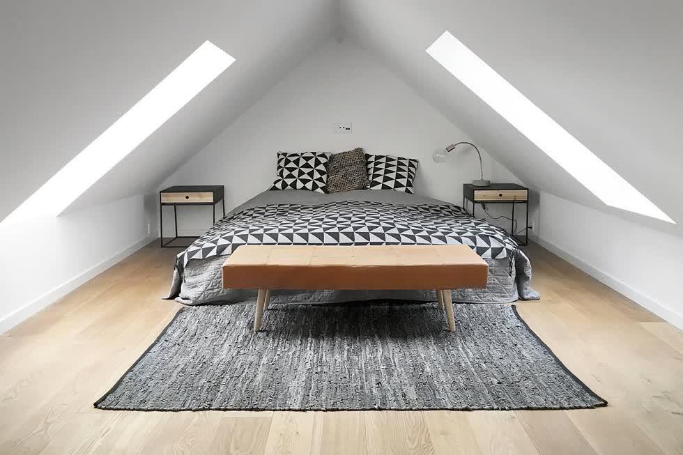 Phòng ngủ gác mái công nghiệp hiện đại với ánh sáng tự nhiên rộng rãi và sàn gỗ đẹp.