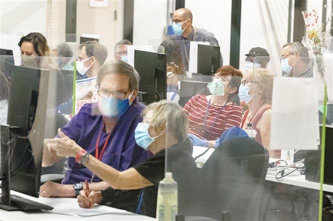 Nhân viên bầu cử kiểm phiếu bầu Tổng thống Mỹ 2020ở Phoenix, bang Arizona sử dụng các biện pháp phòng lây nhiễm. Ảnh: AFP