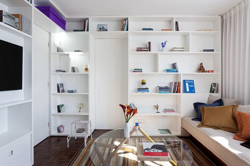 Tủ sách màu trắng bên trong căn hộ 30m2 được giấu ẩn phía sau cửa phòng ngủ.