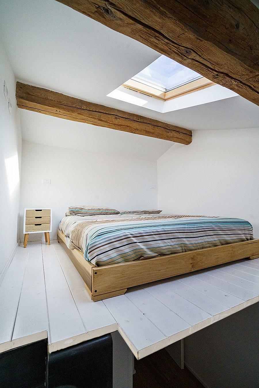 Giếng trời mang ánh sáng tự nhiên vào phòng ngủ công nghiệp nhỏ trên gác mái màu trắng.