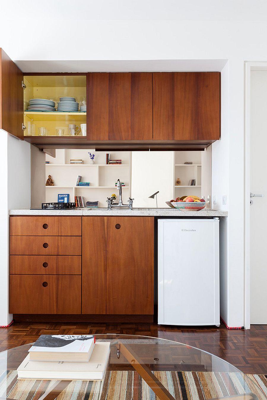 Tủ gỗ màu cánh gián mang lại sự ấm áp cho căn hộ studio nhỏ màu trắng.