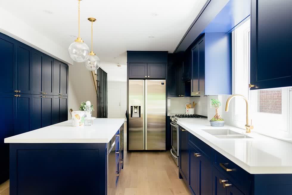 Sự kết hợp giữa màu trắng và xanh nước biển với tay cầm và đồ đạc bằng đồng làm cho căn bếp sang trọng hơn.