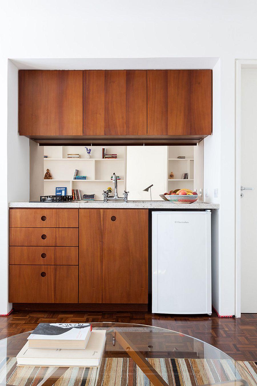Tủ bếp bằng gỗ tạo điểm nhấn ấm áp cho căn hộ màu trắng chủ đạo.