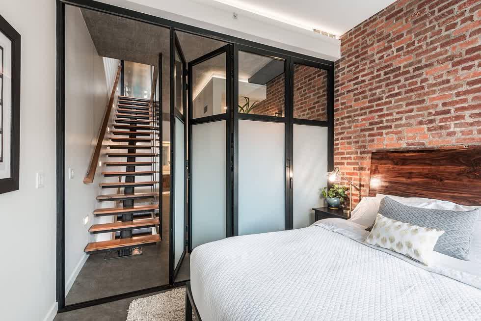 Cửa xếp và phông nền trung tính làm tăng thêm thiết kế rộng rãi của phòng ngủ công nghiệp nhỏ này với bức tường gạch tạo điểm nhấn.