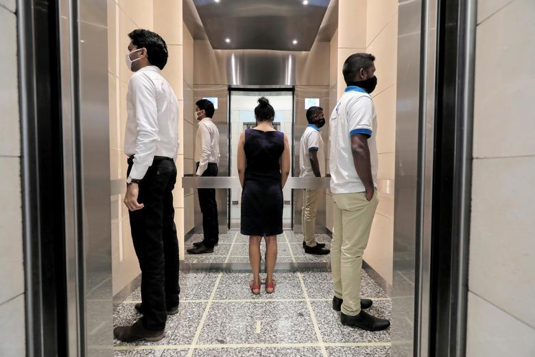 Mọi người thực hành giãn cách xã hội trong thang máy trước khi đến nơi làm việc, sau khi chính phủ Sri Lanka tuyên bố rằng các công ty tư nhân và nhà nước sẽ mở lại văn phòng của họ sau gần hai tháng bị phong tỏa, tại Colombo, ngày 11/5. Ảnh:REUTERS