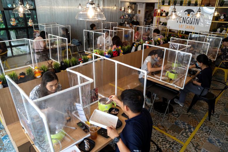 Mọi người dùng bữa trưa tại nhà hàng lẩu Penguin Eat Shabu sau khi nó mở cửa trở lại ở Bangkok, Thái Lan, ngày 8/5. Ảnh: REUTERS