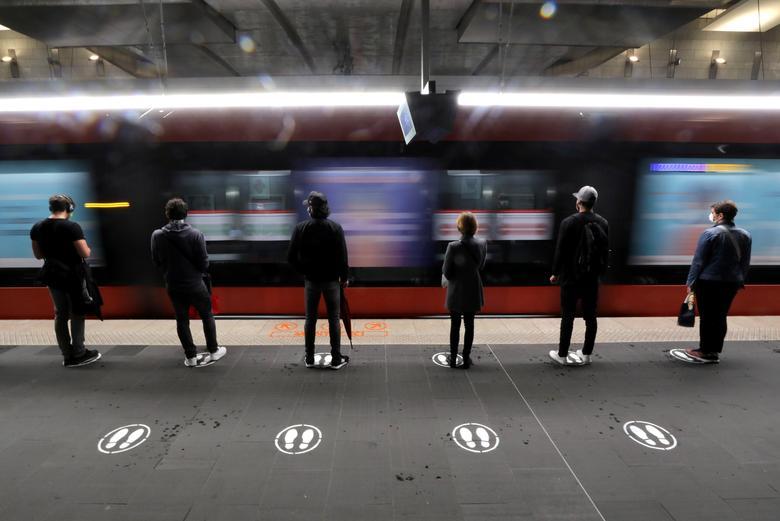 Mọi người đứng trên các biển báo để thực hiện giãn cách xã hội trong khi chờ xe điện ở Nice, Pháp, ngày 11/5. Ảnh: REUTERS