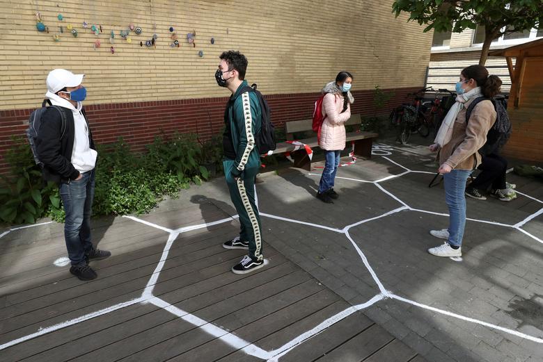 Học sinh nói chuyện trong bối cảnh giãn cách xã hội tại sân của một trường trung học khi mở cửa trở lại ở Brussels, Bỉ, ngày 15/5. Ảnh: REUTERS