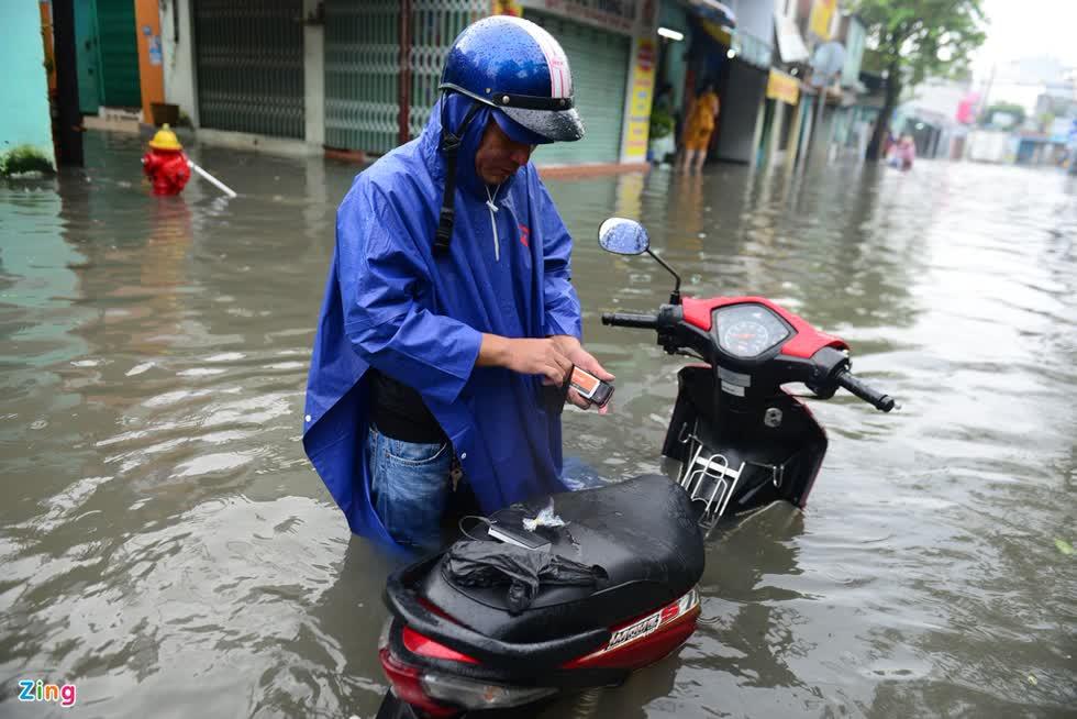 Một người dân vất vả khi đi làm vào buổi sáng trên đường An Dương Vương sau trận mưa cả đêm. Ảnh: Zing