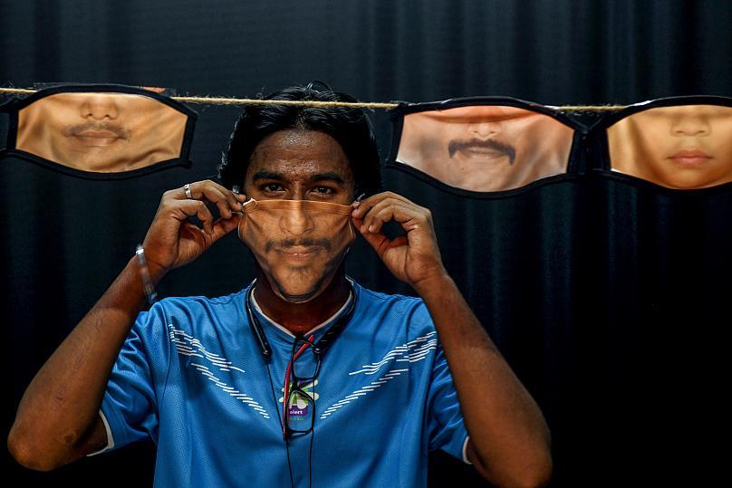 Một người đàn ông điều chỉnh khẩu trang với hình ảnh khuôn mặt được in trên đó khi các khẩu trang khác được treo phía sau. Ảnh chụp tại Chennai, Ấn Độ. Ảnh: AFP.