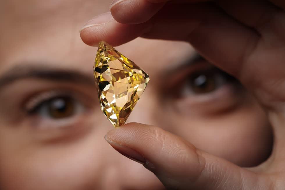 Một nhân viên của Christie với một viên kim cương cắt 118 rực rỡ trước khi bán đấu giá.Ảnh: EPA-EFE.