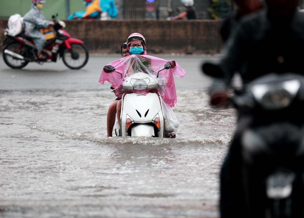 Nước ngập gây khó khăn đến việc lưu thông của người dân. Ảnh: báo Thanh Niên