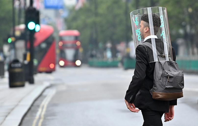 Một người đi bộ mang một thiết bị bảo vệ cá nhân như một biện pháp phòng ngừa chống lại COVID-19, đi bộ qua đường Oxford ở London, Vương quốc Anh. Ảnh: AFP.