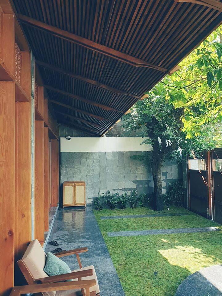Sân vườn mát mẻ với gỗ, đá, cỏ, cây được kết hợp một cách hài hòa, đầy an yên.