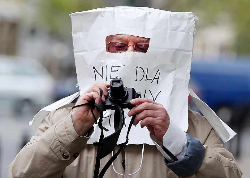 Một nhiếp ảnh gia đeo mặt nạ bảo vệ khác thường chống lại COVID-19 làm từ túi giấy, ở Warsaw, Ba Lan. Ảnh: AP.