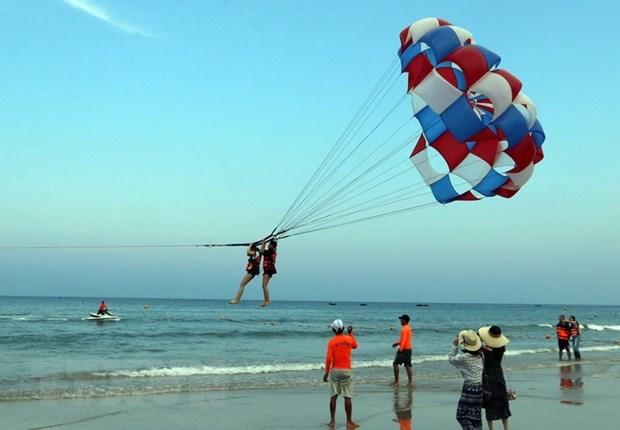 Khách du lịch tham gia trò chơi canô kéo dù tại biển ở Đà Nẵng. Ảnh: TTXVN