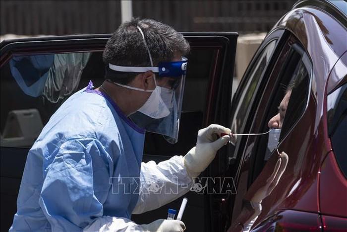 Nhân viên y tế lấy mẫu xét nghiệm COVID-19 cho người dân tại El Paso, bang Texas, Mỹ ngày 18/5. Ảnh: AFP/TTXVN