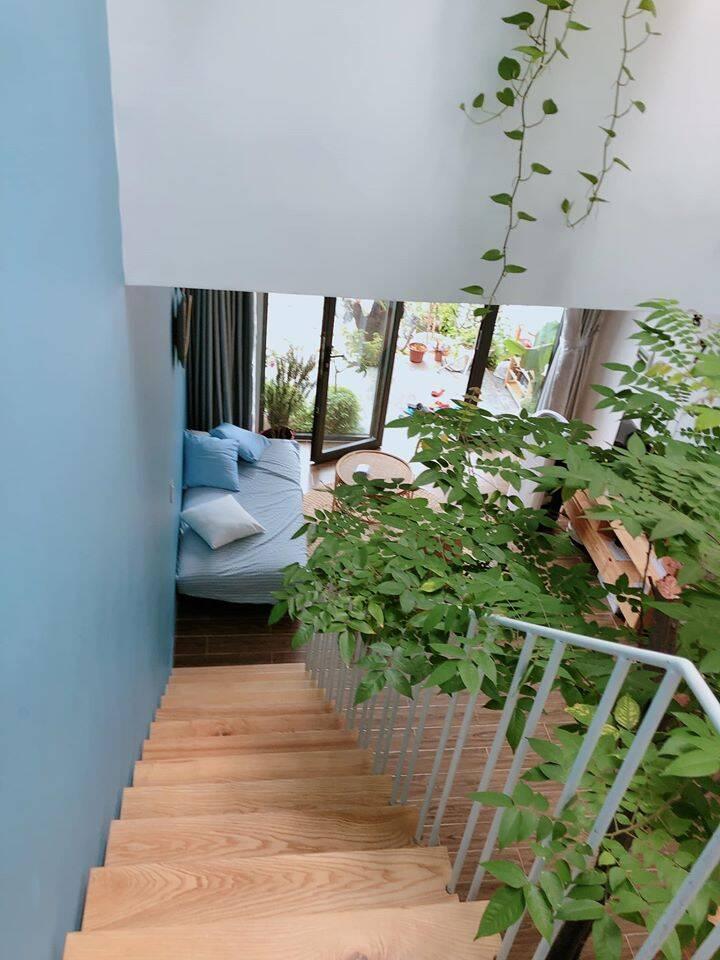 Cầu thang lát gỗ với thiết kế nhỏ gọn, kết hợp với tay vịn màu trắng tạo điểm nhấn.