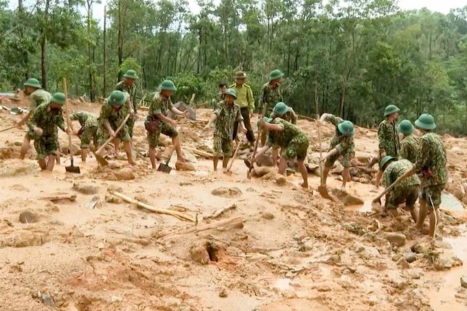 Công bình đào bới tại hiện trường vụ sạt đất ở trạm kiểm lâm 67. Ảnh: VNE