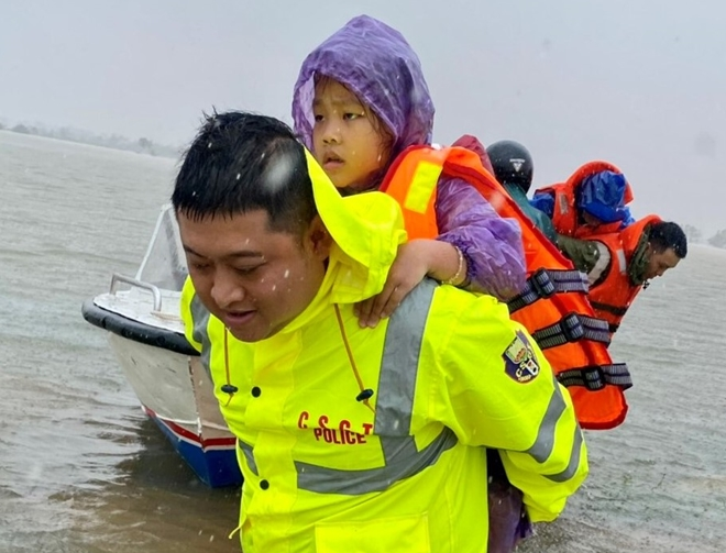 Trẻ nhỏ cũng được các chiến sĩ CAND hỗ trợ di chuyển đến nơi an toàn. Ảnh: CAND