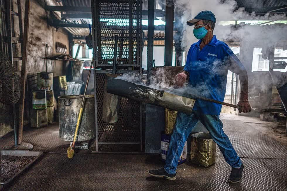 Một công nhân mang hạt cà phê được rang bằng củi tại xưởngAntong. Ảnh: AFP.