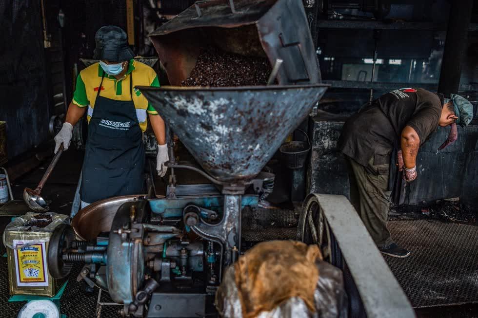 Một công nhân (bên trái) đổ cà phê pha đương vào chiếc hôp thiết để bán tại xưởngcà phê Antong ở Taiping, Malaysia. Ảnh: AFP.