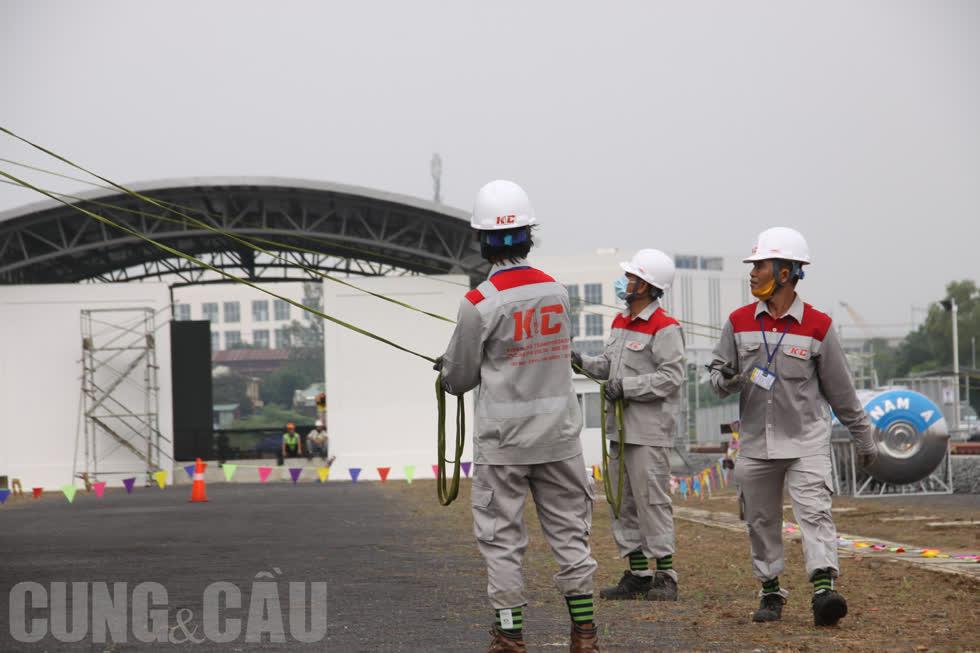 Phía dưới có các nhân viên kỹ thuật kéo dây để cân chỉnh vị trí, đảm bảo độ chính xác và an toàn.