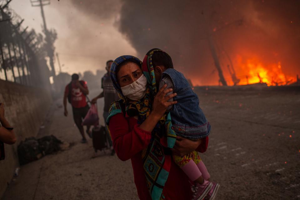 Một phụ nữ bế một đứa trẻ đi qua đống lửa sau khi đám cháy lớn bùng phát ở trại di cư Moria trên đảo Lesbos của Hy Lạp Aegean vào ngày 9/9. Ảnh: Getty.