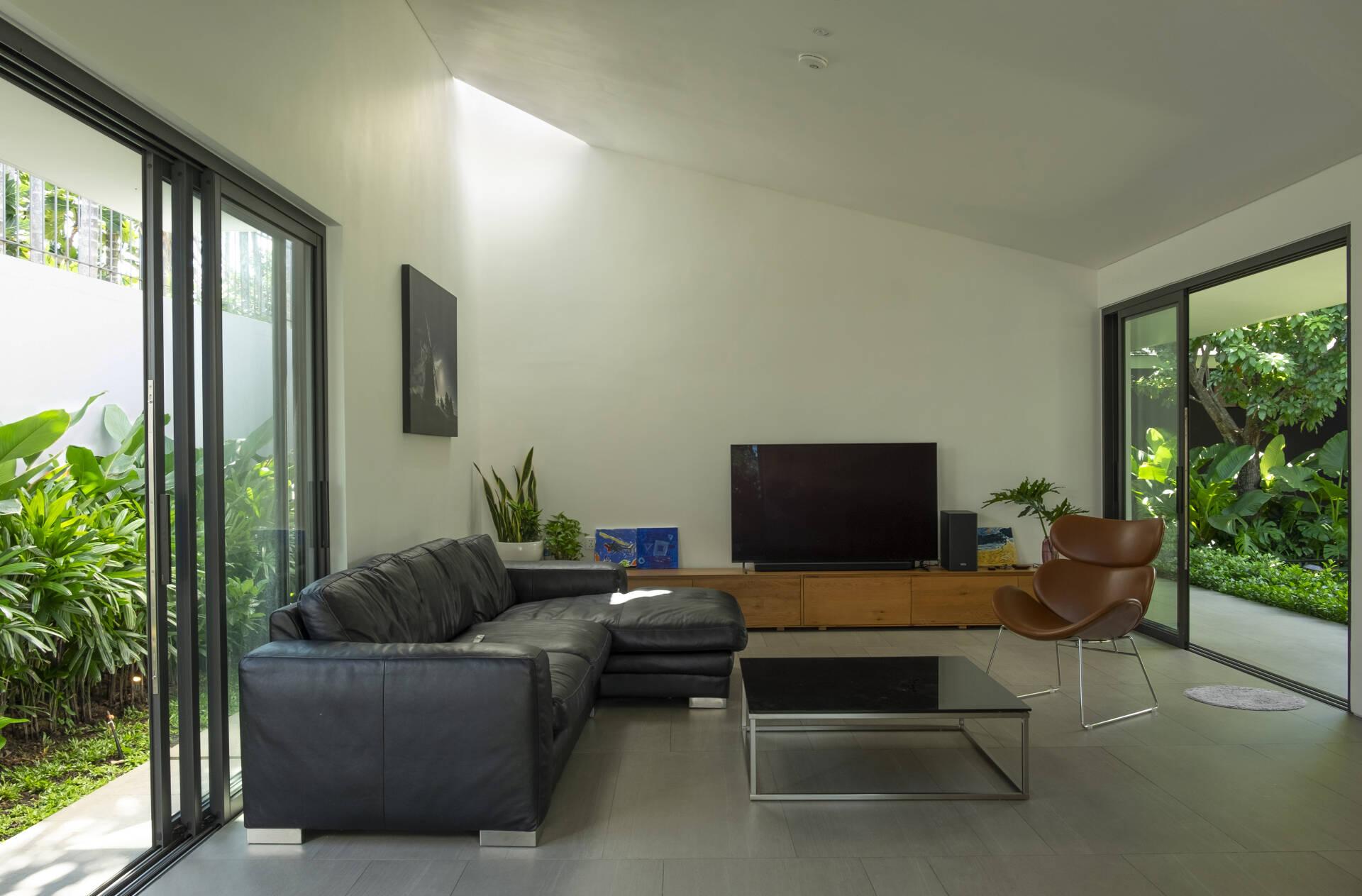 Phòng khách với thiết kế đơn giản, hiện đại, sở hữu không gian thông thoáng nhờ hai khoảng sân vườn trước.