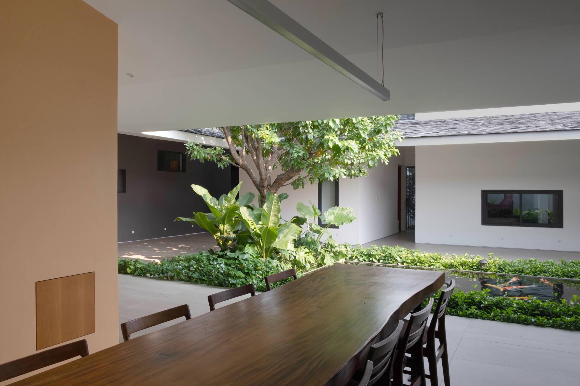Khu vực bàn ghế ăn nằm giữa phòng khách và phòng bếp, kết nối trực tiếp với không gian chung giữa nhà mà không có vách ngăn.
