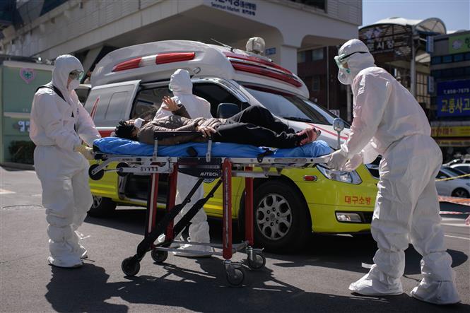 Nhân viên y tế chuyển bệnh nhân mắc COVID-19 vào một bệnh viện ở Daegu, Hàn Quốc. Ảnh: TTXVN.