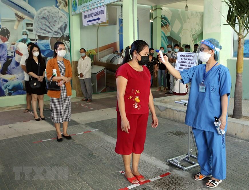 Người dân đến khám bệnh được đo nhiệt độ, khai báo y tế trước khi vào khu vực khám tại Bệnh viện Đà Nẵng. Ảnh: TTXVN