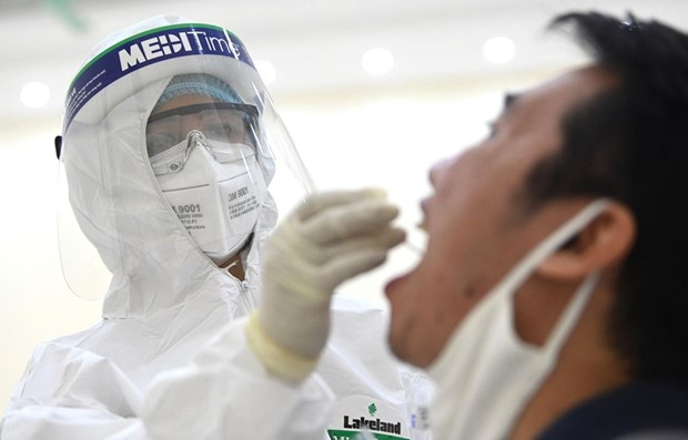 Nhân viên y tế tiến hành lấy mẫu dịch hầu họng để xét nghiệm bằng phương pháp RT-PCR. Ảnh: TTXVN.