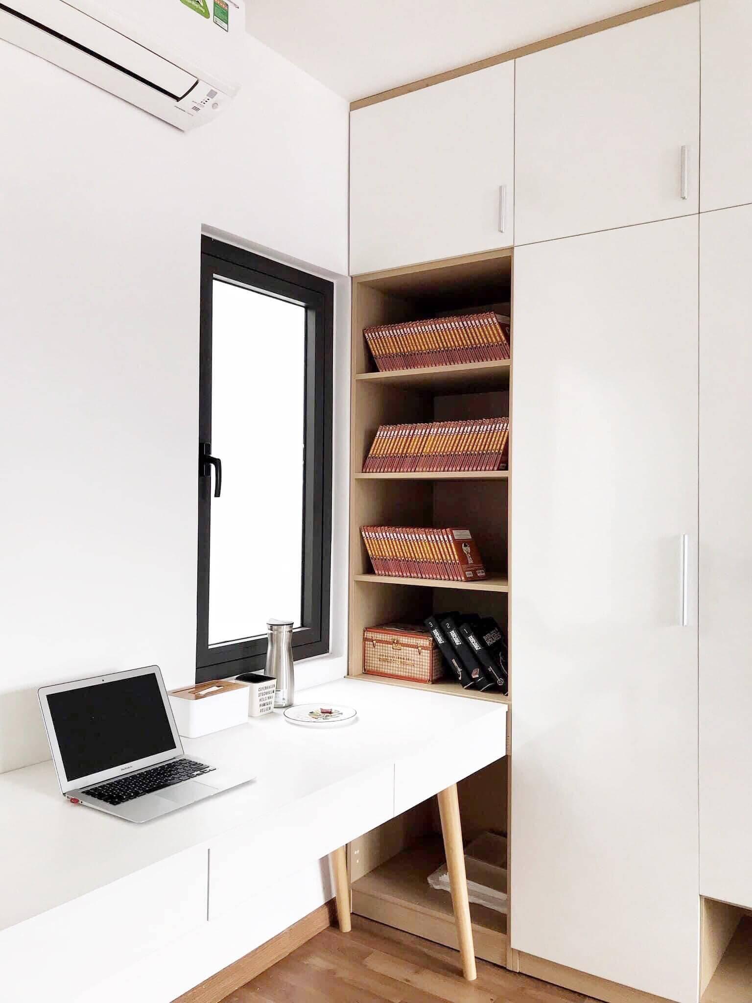 Góc làm việc cùng tủ cao sát trần để đồ dùng, sách truyện bên cạnh.