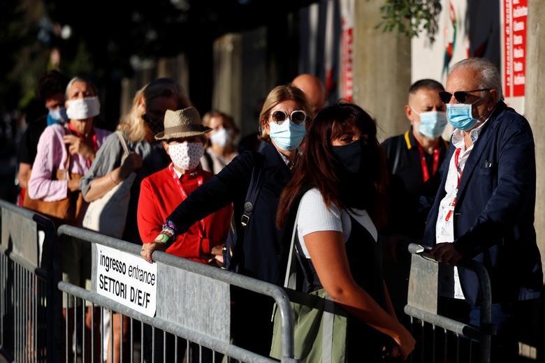 Những người đeo khẩu trang bảo hộ xếp hàng trước khi vào xem buổi chiếu đầu tiên của Liên hoan phim quốc tế Venice lần thứ 77. Ảnh: Reuters.