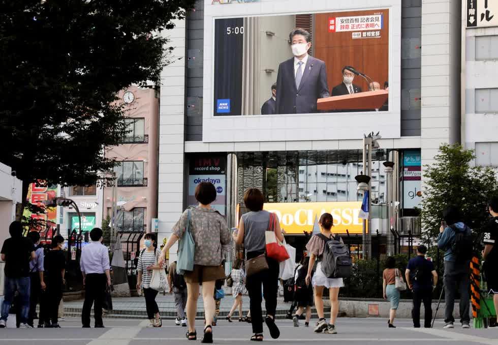 Người dân đeo khẩu trang bảo vệ xem buổi phát sóng cuộc họp báo của Thủ tướng Nhật Bản Shinzo Abe tại Tokyo, Nhật Bản vào chiếu 28/8. Ảnh: Reuters.