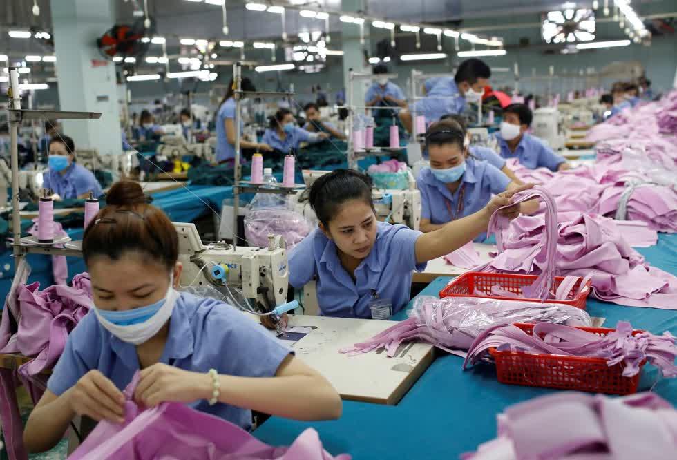 Công nhân làm việc tại một dây chuyền sản xuất may mặc ở TP.HCM. Ảnh: Reuters.