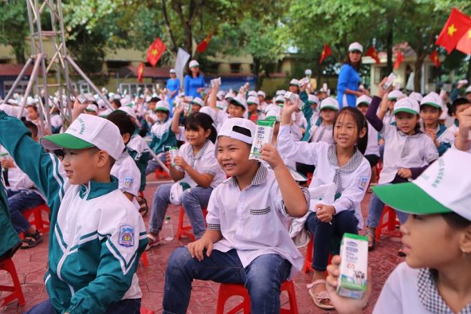 Các em học sinh Trường Tiểu học A hào hứng tham gia hoạt động uống sữa cùng các bạn tại sân trường trong buổi lễ phát động